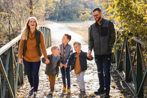 Young Family of Five Smiling on Bridge